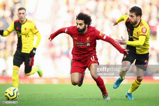 Mohamed Salah of Liverpool holds off Kiko Femenia of Watford during the Premier League match between Liverpool FC and Watford FC at Anfield on...