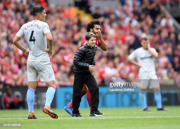 Mohamed Salah of Liverpool hugs a young fan during the Premier League match between Liverpool FC and West Ham United at Anfield on August 12 2018 in...