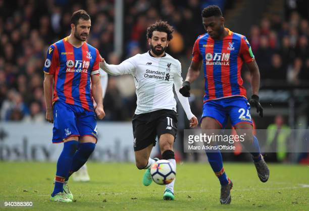 Mohamed Salah of Liverpool in action with Luka Milivojevic and Timothy FosuMensah of Crystal Palace during the Premier League match between Crystal...