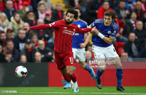 Mohamed Salah of Liverpool is challenged by Caglar Soyuncu of Leicester City during the Premier League match between Liverpool FC and Leicester City...