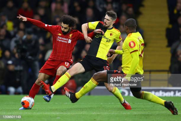 Mohamed Salah of Liverpool is challenged by Craig Cathcart and Christian Kabasele of Watford during the Premier League match between Watford FC and...