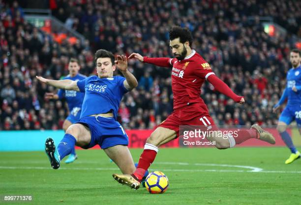 Mohamed Salah of Liverpool is challenged by Harry Maguire of Leicester City during the Premier League match between Liverpool and Leicester City at...