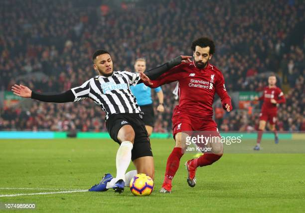 Mohamed Salah of Liverpool is challenged by Jamaal Lascelles of Newcastle United during the Premier League match between Liverpool FC and Newcastle...