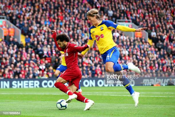 Mohamed Salah of Liverpool is challenged by Jannik Vestergaard of Southampton during the Premier League match between Liverpool FC and Southampton FC...