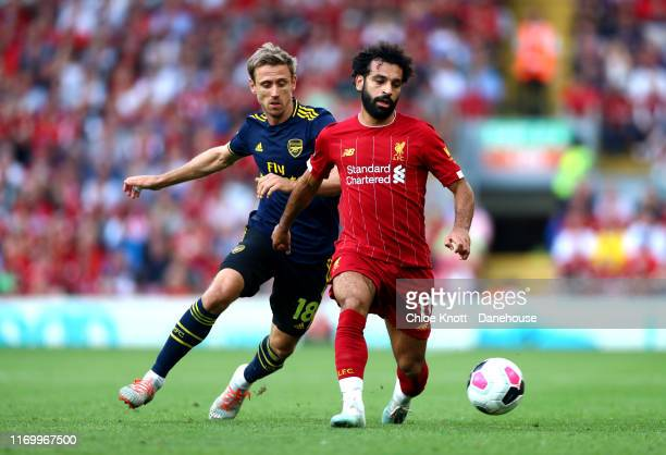 Mohamed Salah of Liverpool is challenged by Nacho Monreal of Arsenal during the Premier League match between Liverpool FC and Arsenal FC at Anfield...