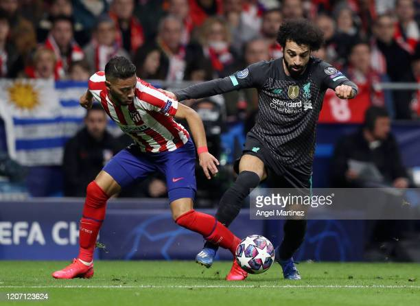 Mohamed Salah of Liverpool is challenged by Renan Lodi of Atletico Madrid during the UEFA Champions League round of 16 first leg match between...