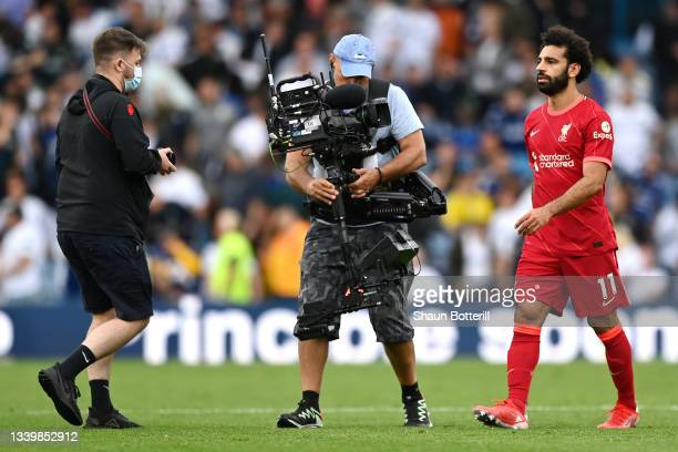 Mohamed Salah of Liverpool is filmed by a TV camera operator as a pitch invader attempts to speak with him at the end of the first half during the...