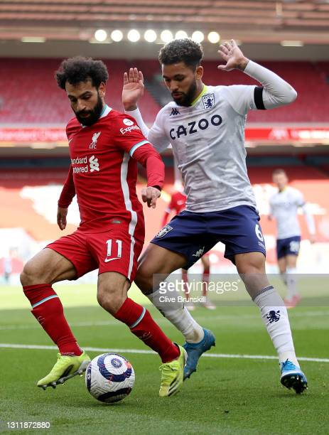 Mohamed Salah of Liverpool is put under pressure by Douglas Luiz of Aston Villa during the Premier League match between Liverpool and Aston Villa at...