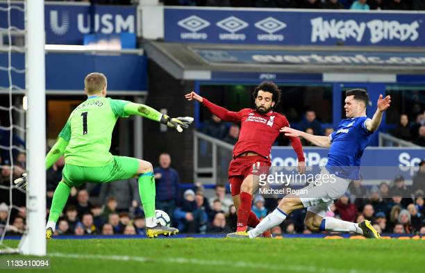 Mohamed Salah of Liverpool is tackled by Michael Keane of Everton as Jordan Pickford looks on during the Premier League match between Everton FC and...