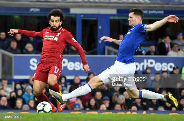 Mohamed Salah of Liverpool is tackled by Michael Keane of Everton during the Premier League match between Everton FC and Liverpool FC at Goodison...