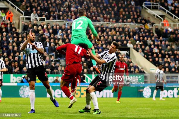 Mohamed Salah of Liverpool Martin Dubravka and Fabian Schar both of Newcastle United battle for the ball during the Premier League match between...