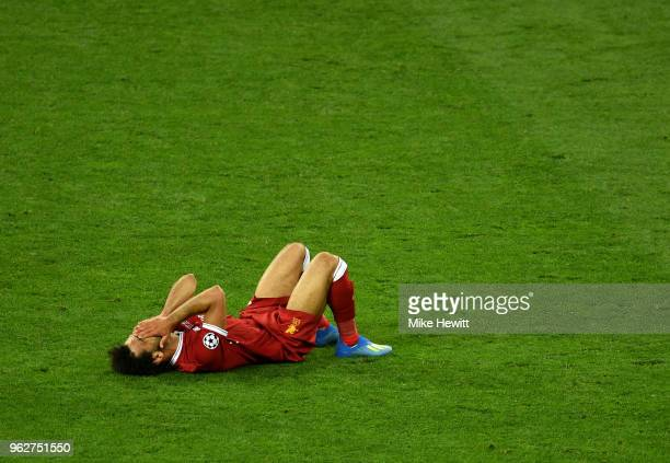 Mohamed Salah of Liverpool reacts as he goes down injured during the UEFA Champions League Final between Real Madrid and Liverpool at NSC Olimpiyskiy...