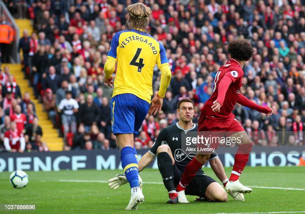 Mohamed Salah of Liverpool reacts to his shot as Alex McCarthy of Southampton looks on during the Premier League match between Liverpool FC and...