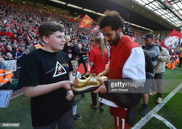 Mohamed Salah of Liverpool receives the golden boot off a Liverpool fan at the end of the Premier League match between Liverpool and Brighton and...