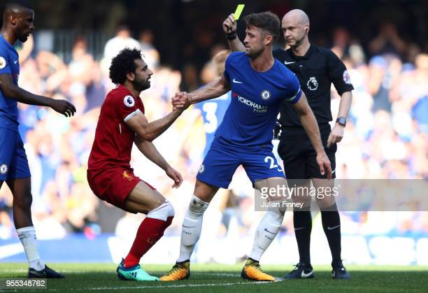 Mohamed Salah of Liverpool recieves a yellow card from match referee Anthony Taylor as Gary Cahill of Chelsea picks up Mohamed Salah of Liverpool...
