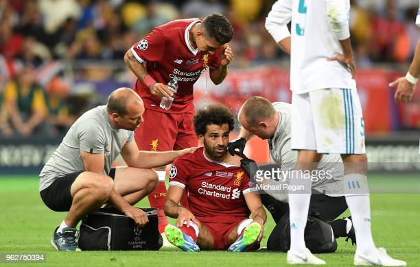 Mohamed Salah of Liverpool recieves medical treatment after he goes down injured during the UEFA Champions League Final between Real Madrid and...