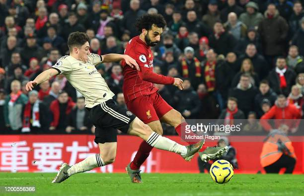 Mohamed Salah of Liverpool scores his team's second goal past David De Gea of Manchester United as he is challenged by Daniel James of Manchester...