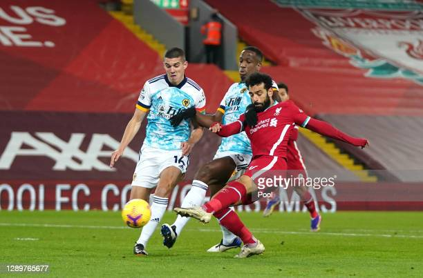 Mohamed Salah of Liverpool scores their sides first goal whilst under pressure from Conor Coady and Willy Boly of Wolverhampton Wanderers during the...