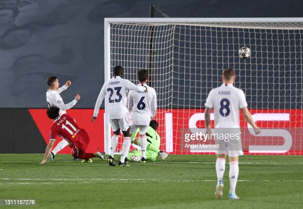 Mohamed Salah of Liverpool scores their team's first goal past Lucas Vazquez, Ferland Mendy, Nacho Fernandez and Thibaut Courtois of Real Madrid...