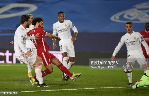 Mohamed Salah of Liverpool scores their team's first goal past Lucas Vazquez, Ferland Mendy and Nacho Fernandez of Real Madrid during the UEFA...