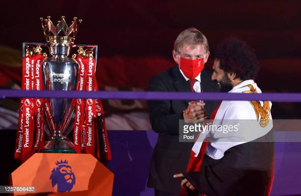 Mohamed Salah of Liverpool shakes hands with Sir Kenny Dalglish Former Captain and Manager of Liverpool upon receiving a Premier League Winner's...