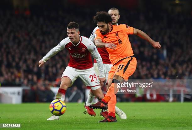 Mohamed Salah of Liverpool shoots as Granit Xhaka of Arsenal looks on during the Premier League match between Arsenal and Liverpool at Emirates...