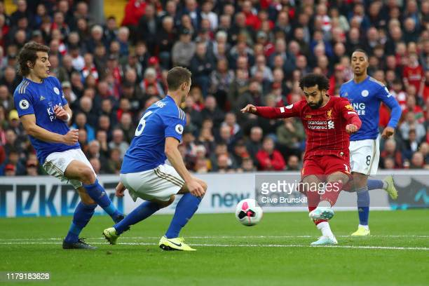 Mohamed Salah of Liverpool shoots as Jonny Evans of Leicester City attempts to block during the Premier League match between Liverpool FC and...
