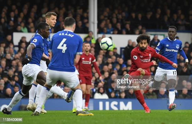 Mohamed Salah of Liverpool shoots past Michael Keane and Kurt Zouma of Everton during the Premier League match between Everton FC and Liverpool FC at...