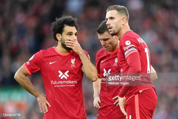 Mohamed Salah of Liverpool speaks with teammates James Milner and Jordan Henderson during the Premier League match between Liverpool and Manchester...