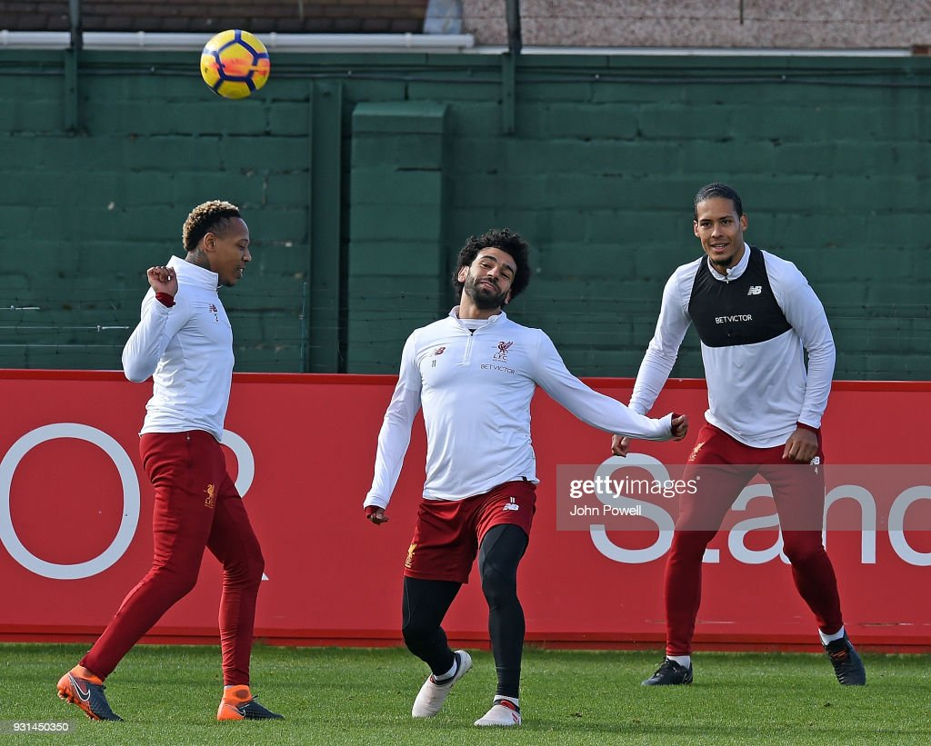 Mohamed Salah with Virgil van Dijk and Nathaniel Clyne of Liverpool during a training session at Melwood Training Ground on March 13, 2018 in Liverpool, England.