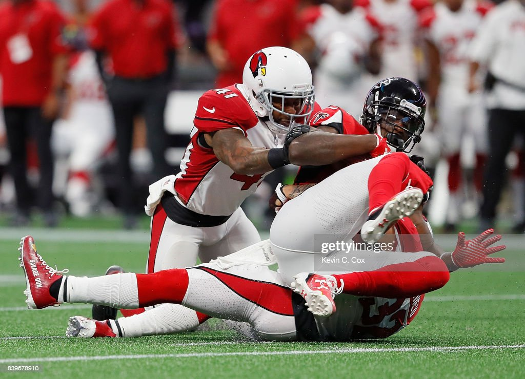 Mohamed Sanu #12 of the Atlanta Falcons is tackled by Antoine Bethea #41 and Tyrann Mathieu #32 of the Arizona Cardinals at Mercedes-Benz Stadium on August 26, 2017 in Atlanta, Georgia.