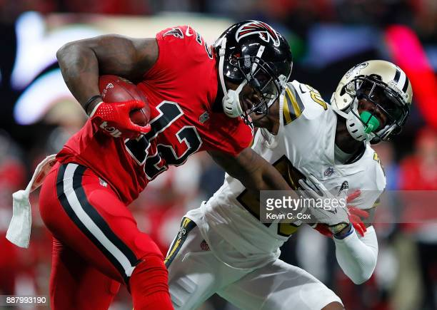 Mohamed Sanu of the Atlanta Falcons tries to break a tackle by Ken Crawley of the New Orleans Saints at MercedesBenz Stadium on December 7 2017 in...