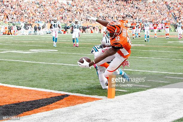 Mohamed Sanu of the Cincinnati Bengals dives to score a touchdown while being hit by Melvin White of the Carolina Panthers during the fourth quarter...