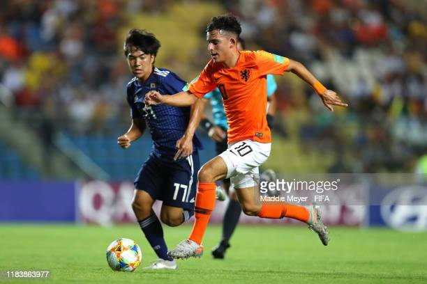 Mohamed Taabouni of Netherlands dribbles past Satoshi Tanaka of Japan during the Group D Match between Japan and Netherlands in the FIF U-17 World...