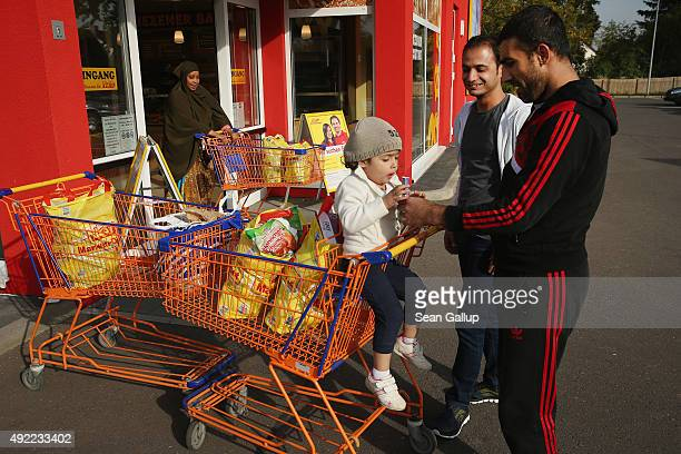 Mohamed Zayat a refugee from Syria offers his daughter Ranim who is nearly 3 candy after shopping for food with fellowSyrian refugee Fadi Almasalmeh...