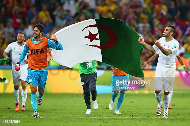 Mohamed Zemmamouche and Essaid Belkalem of Algeria celebrate with a flag after a 11 draw during the 2014 FIFA World Cup Brazil Group H match between...