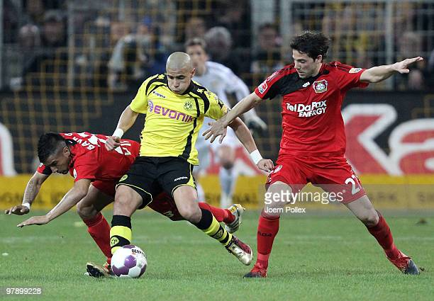 Mohamed Zidan of Dortmund and Tranquillo Barnetta and Gonzalo Castro of Leverkusen compete for the ball during the Bundesliga match between Borussia...