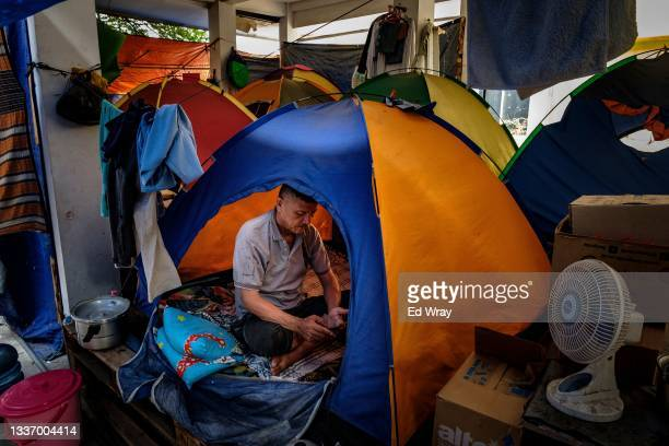 Mohammad, a former teacher from Helmand province, Afghanistan sits in his tent at a facility set up by the Indonesian government for Afghan refugees...