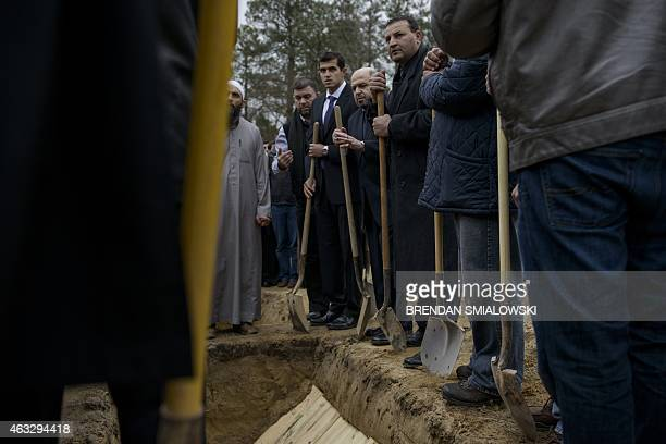 Mohammad AbuSalha father of shooting victims Yusor AbuSalha and Razan Mohammad AbuSalha is joined by loved ones during a burial February 12 2015 in...