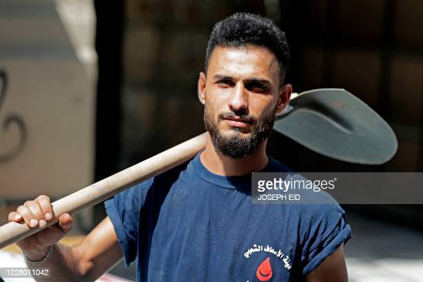Mohammad Ahmad poses for a picture while helping as a volunteer in the cleanup of the Gemmayzeh neighbourhood of Lebanon's capital Beirut on August...