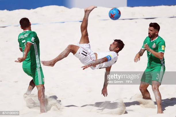Mohammad Ahmadzadeh of Iran attempts a bicycle kick between Ramon Maldonado and Carlos Hernandez of Mexico during the FIFA Beach Soccer World Cup...