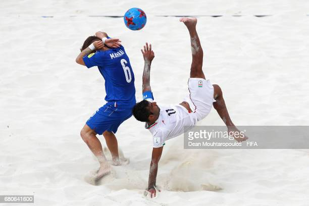 Mohammad Ahmadzadeh of Iran attempts a scissor or bicycle kick shot on goal in front of Simone Marinai of Italy during the FIFA Beach Soccer World...