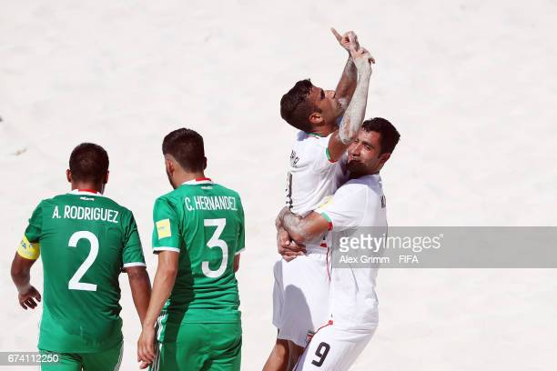 Mohammad Ahmadzadeh of Iran celebrates his team's third goal with team mate Mohammad Mokhtari as Angel Rodriguez and Carlos Hernandez of Mexico react...