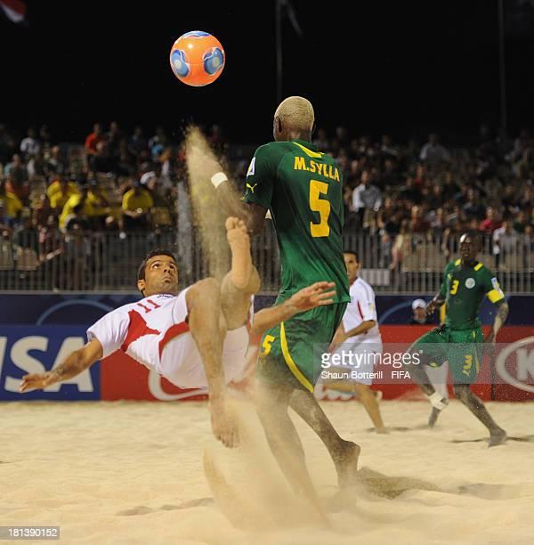 Mohammad Ahmadzadeh of Iran shoots past Mamadou Sylla of Senegal tp score during the FIFA Beach Soccer World Cup Tahiti 2013 Group C match between...