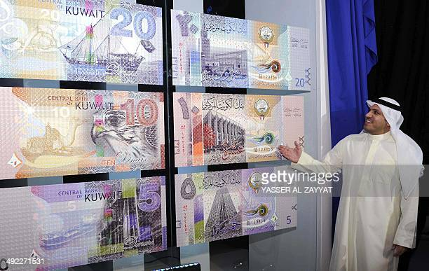 Mohammad alHashel Governor of the Central Bank of Kuwait shows pictures of Kuwait's new banknotes during an official ceremony in Kuwait City on May...