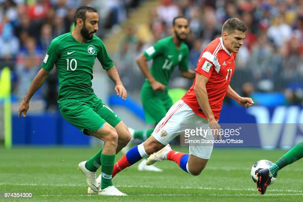 Mohammad AlSahlawi of Saudi Arabia tackles Roman Zobnin of Russia during the 2018 FIFA World Cup Russia group A match between Russia and Saudi Arabia...