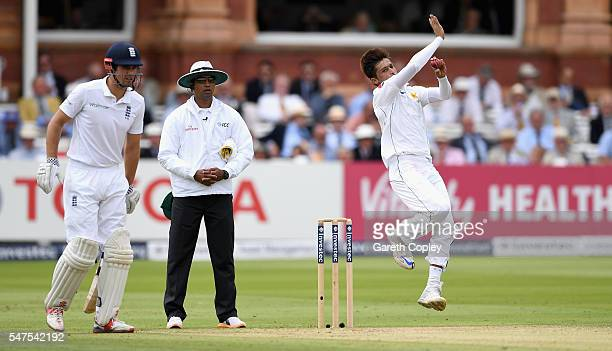 Mohammad Amir of Pakistan bowls alongside England captain Alastair Cook during day two of the 1st Investec Test between England and Pakistan at...