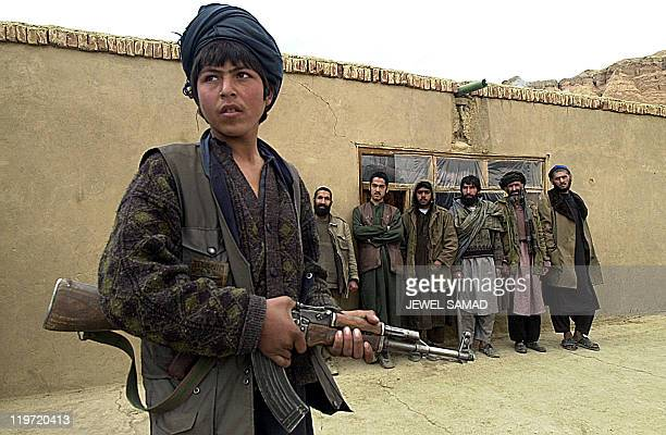 one name an Afghan Northern Alliance soldier keeps guard over Taliban prisoners at a jail in Bamiyan 05 February 2002 Scores of Pakistani and Afghan...