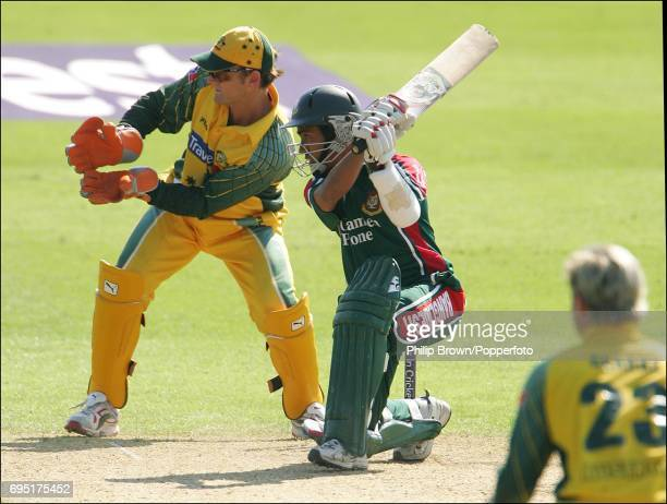 Mohammad Ashraful of Bangladesh hits out watched by Australian wicketkeeper Adam Gilchrist during the NatWest Series One Day International between...