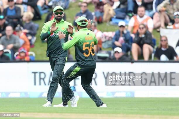Mohammad Hafeez and Babar Azam of Pakistan celebrate the dismissal of Kane Williamson of New Zealand during the third game of the One Day...